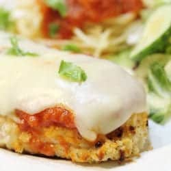 Closeup of plated chicken parmesan showing crispy chicken, layer of sauce and melted cheese.