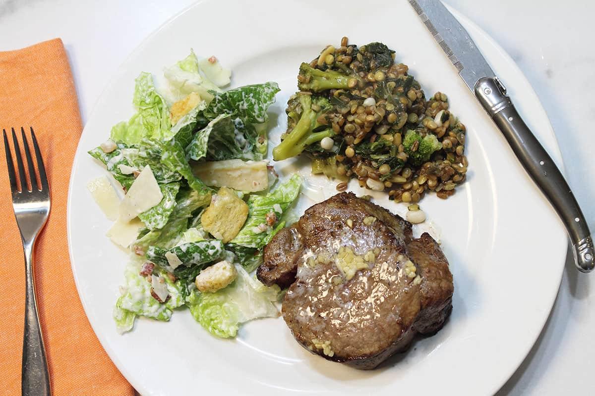 Overhead air fryer steak dinner on white plate.