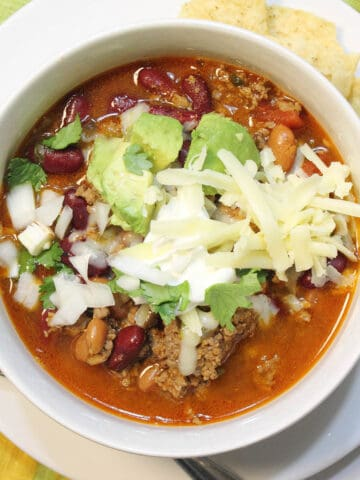 Overhead of white bowl of chili with cheese avocado and sour cream.