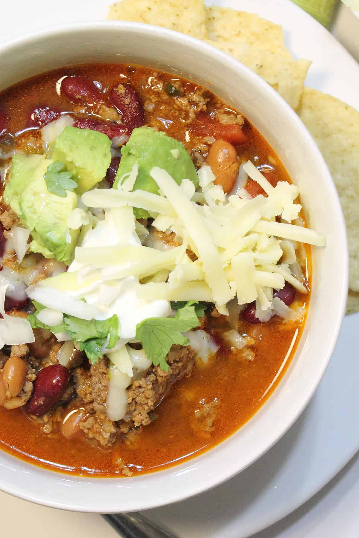 Overhead of partial bowl of slow cooker taco chili topped with cheese, avocado and sour cream.