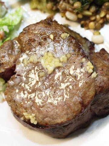 Overhead of steak on dinner plate.