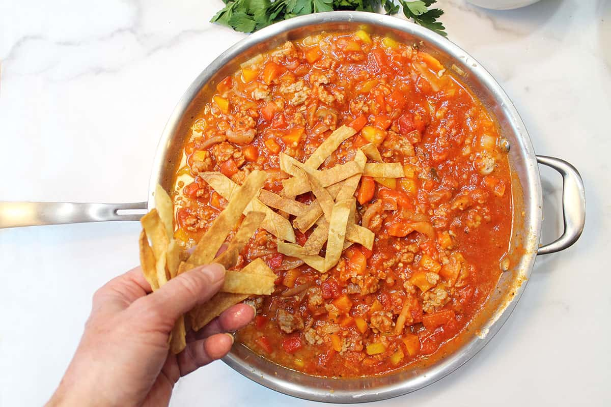 Tossing crispy corn chips on rich tomato sauce based turkey chili.