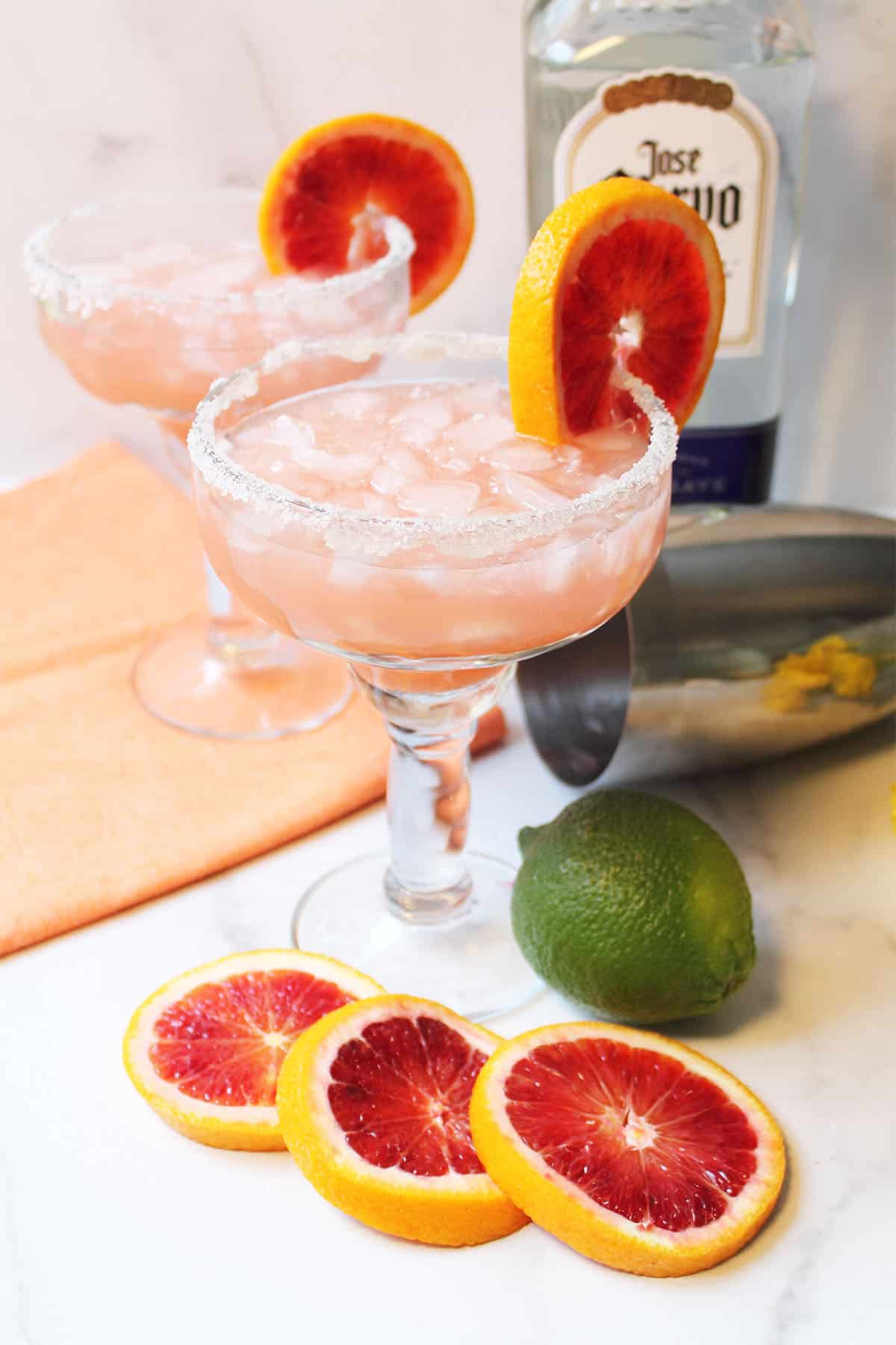 Two cocktails with blood orange garnish on white table.
