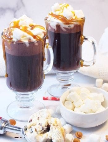 Two melted ice cream hot chocolates with caramel sauce with marshmallows on the table.