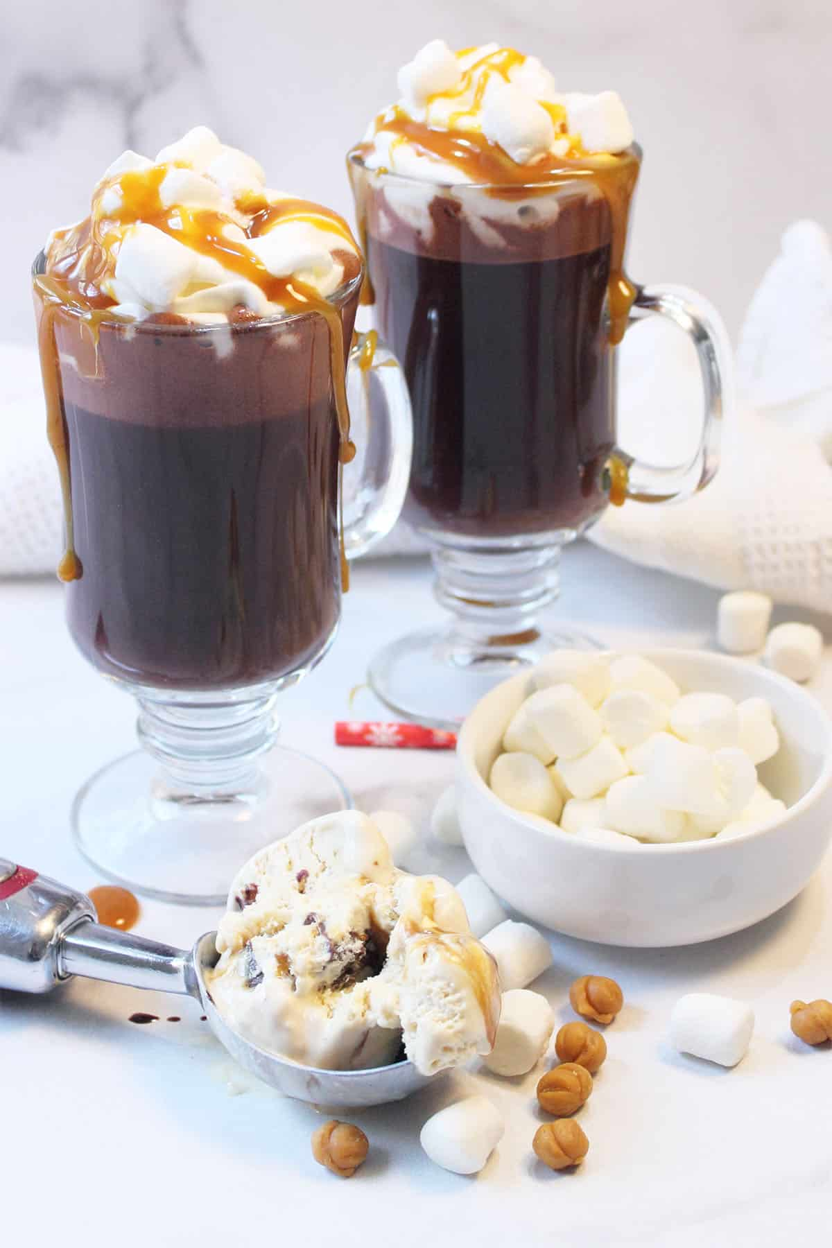 Two hot chocolates with whipped cream and caramel sauce with scoop of ice cream and marshmallows on the table.