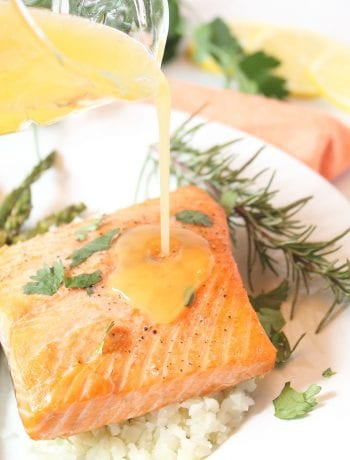 Drizzling butter sauce over air fryer salmon.