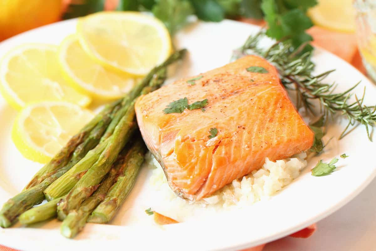 Salmon dinner with asparagus and lemon slices on white plate.