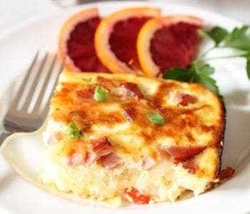 Slice of casserole on white plate with fork beside it.