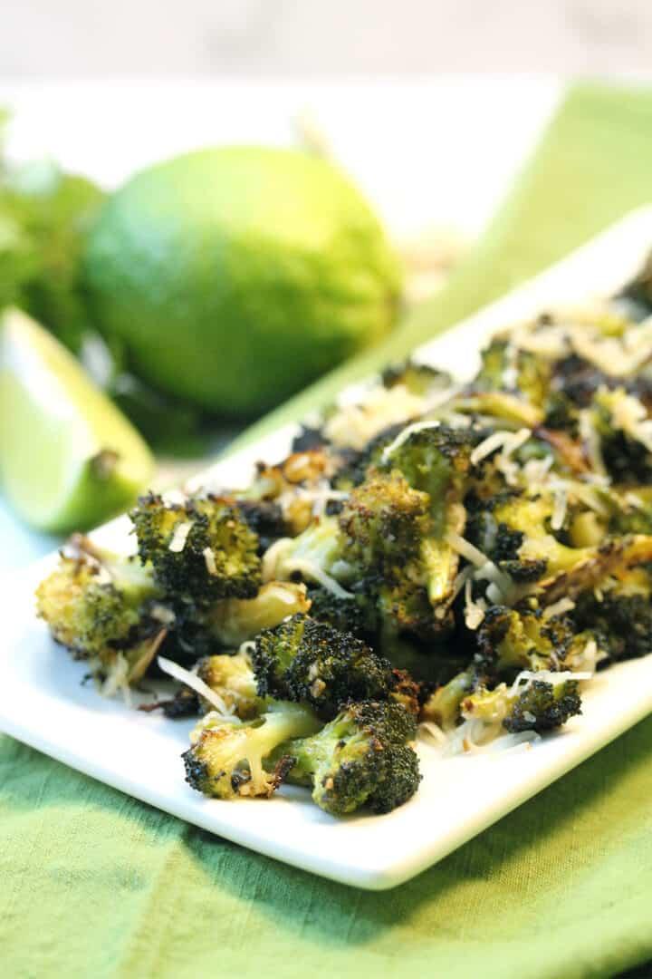 Closeup of platter of roasted broccoli on green napkin.