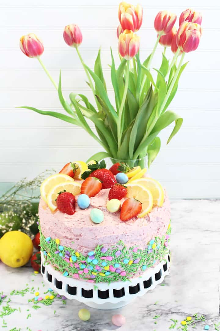 Decorated cake with sprinkle on side in front of tulips.