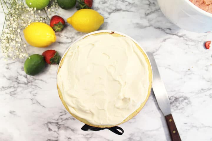 Spreading lemon cream filling on bottom cake layer.
