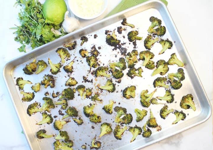 Overhead of roasted broccoli on baking sheet.