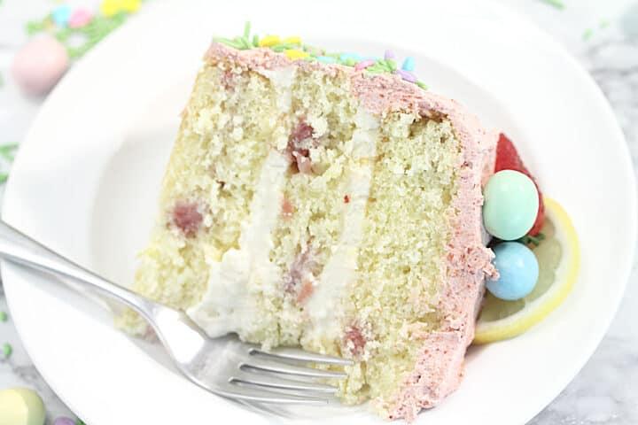 Closeup of slice of lemon cake on white plate with pastel candy and lemon slice garnish.