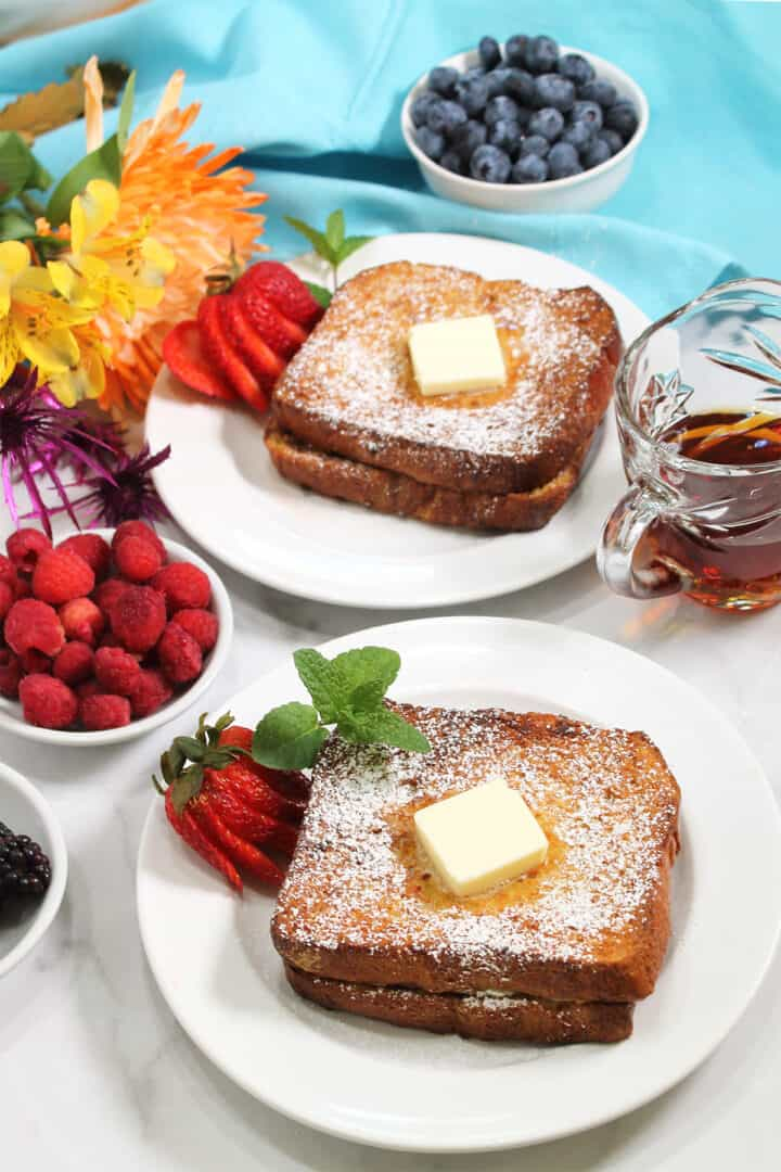 Two servings of Stuffed French Toast on white plates with berries, flowers and syrup beside them.
