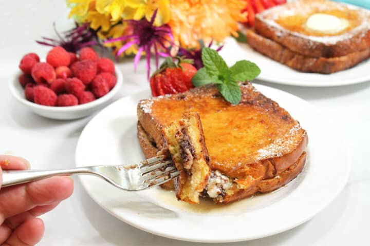 Bite on fork over plate with flowers  in back.