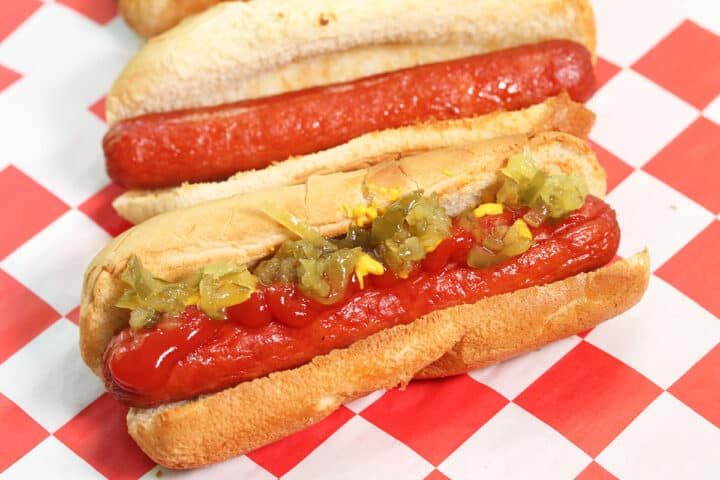 Closeup of dressed hot dog on red checkered paper.