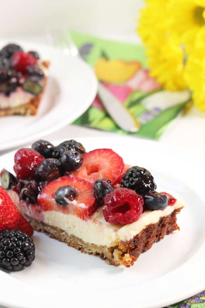 Closeup of slice of fruit topped tart on plate.