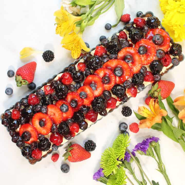Fresh Fruit Tart on marble table with flowers and fruit around it.