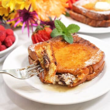 Holding bite of French Toast on fork over plated breakfast.