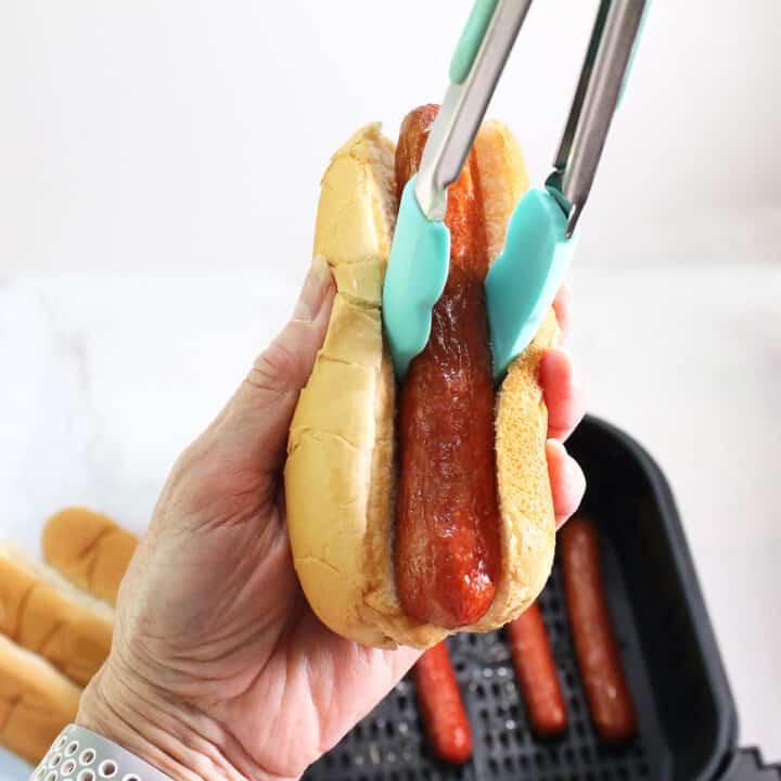 Placing air fried hot dog in bun.