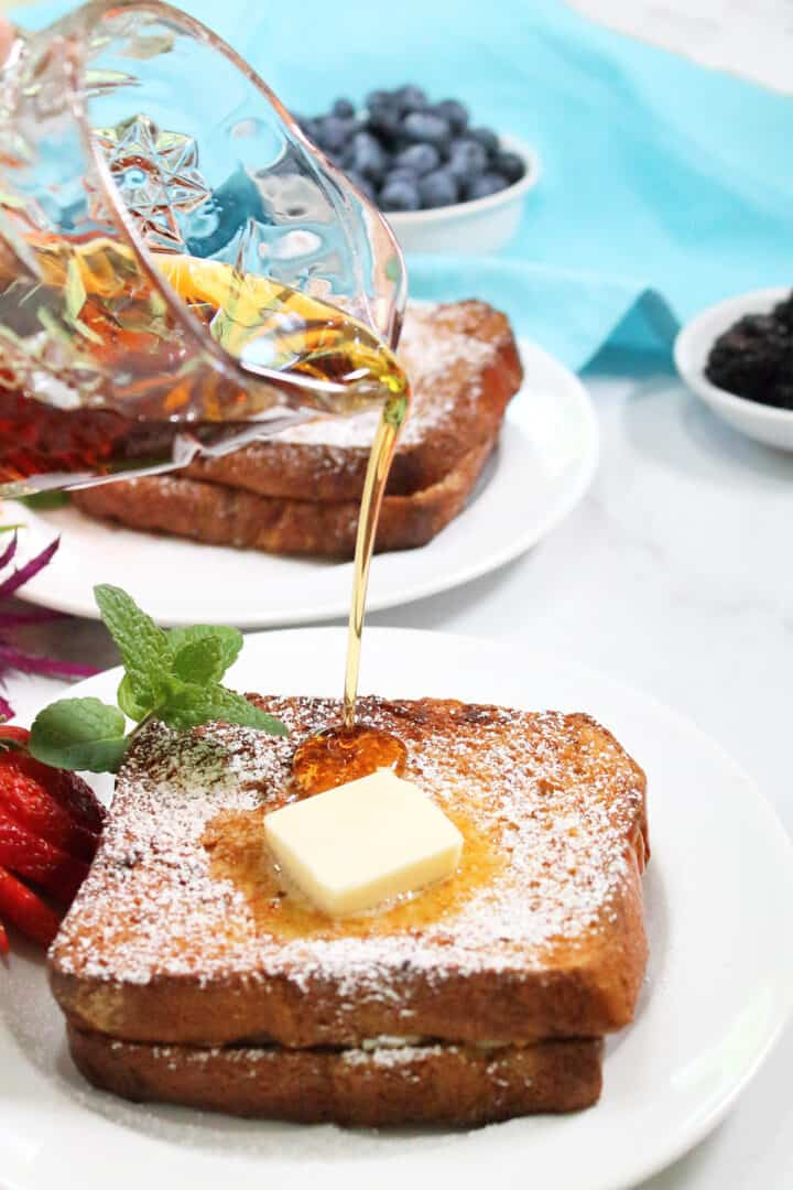 Pouring syrup over plated Cannoli Stuffed French Toast.