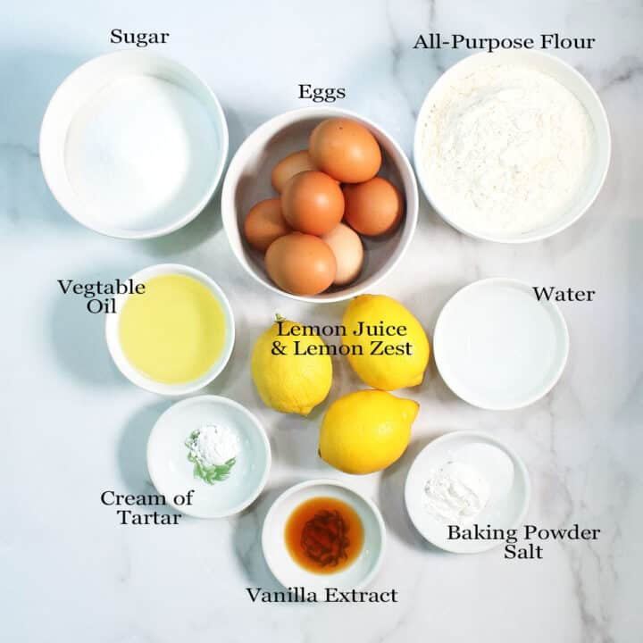 Overhead of lemon chiffon cake ingredients on marble table.