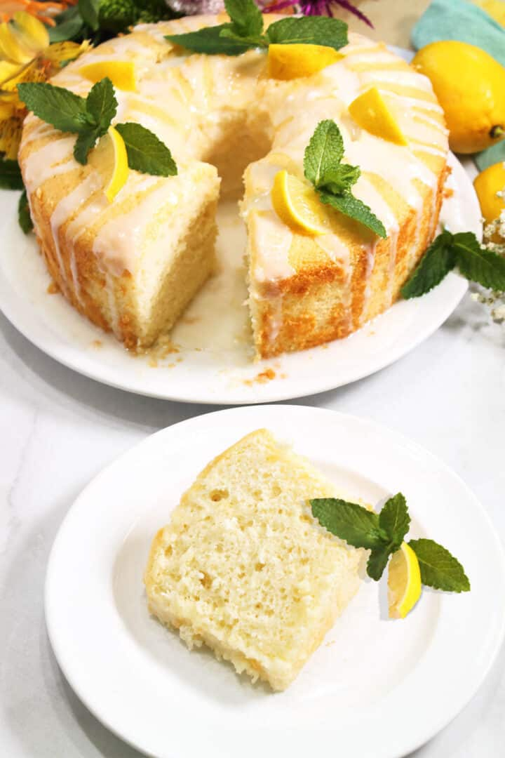 Slice of lemon chiffon cake on white plate with whole cake in background.