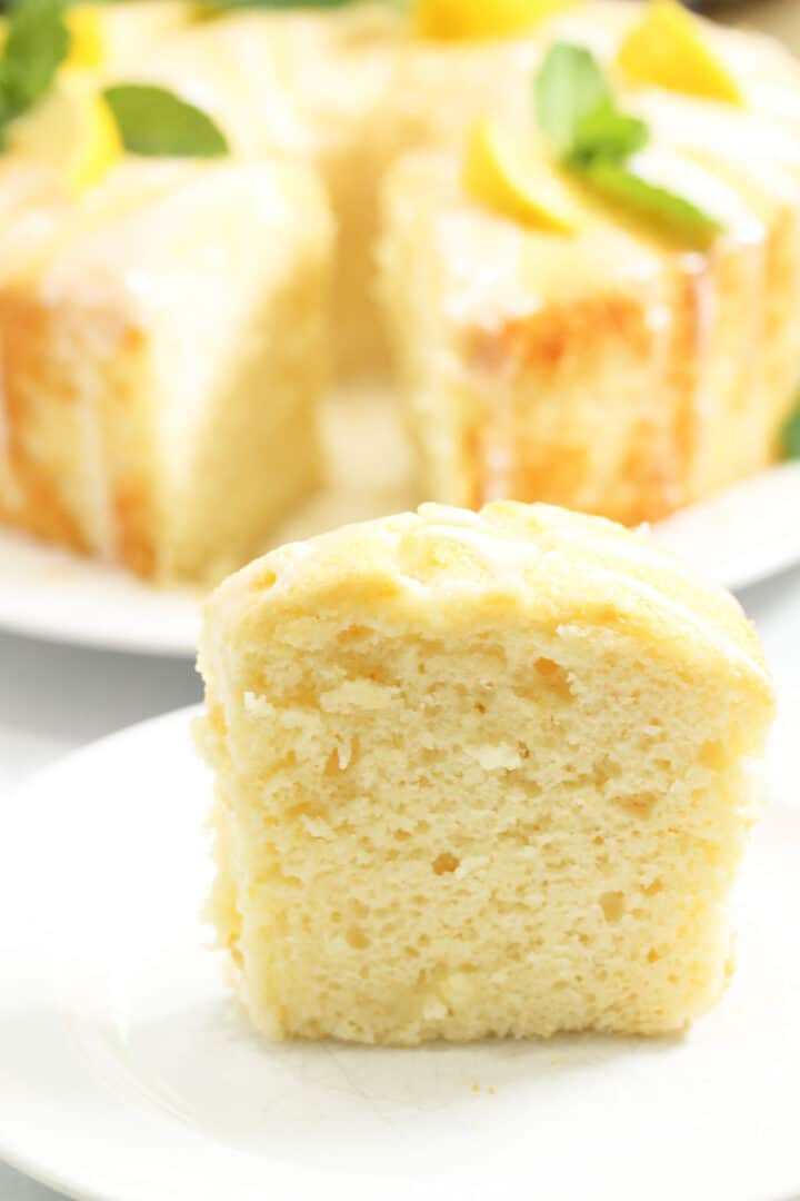 Closeup of slice of lemon cake with whole cake in background.