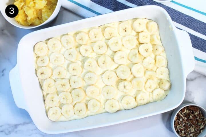 Overhead of sliced bananas on custard.