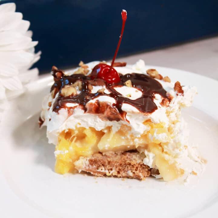 Serving of sliced no bake banana split dessert on white plate showing layers.