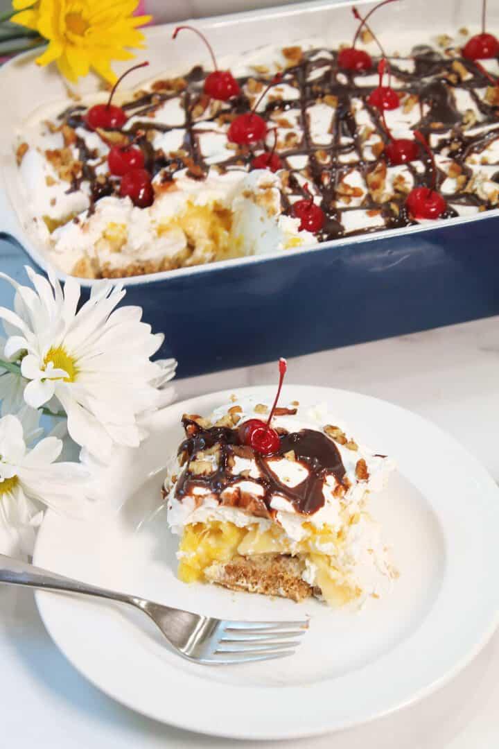 Slice of Banana Split Cake on plate with full dessert in back.