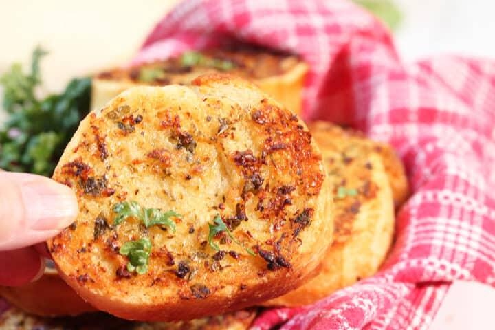 Closeup holding air fried garlic bread over basket.