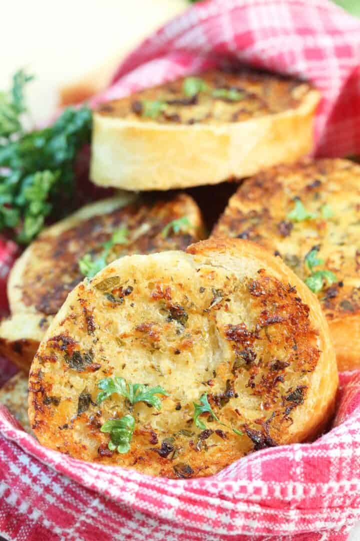 Closeup of garlic bread in basket lined with red checkered linen.
