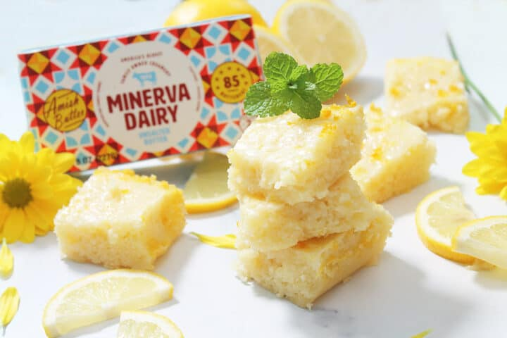 Stacked and scattered lemon blondies on marble table with Minerva Dairy butter package.