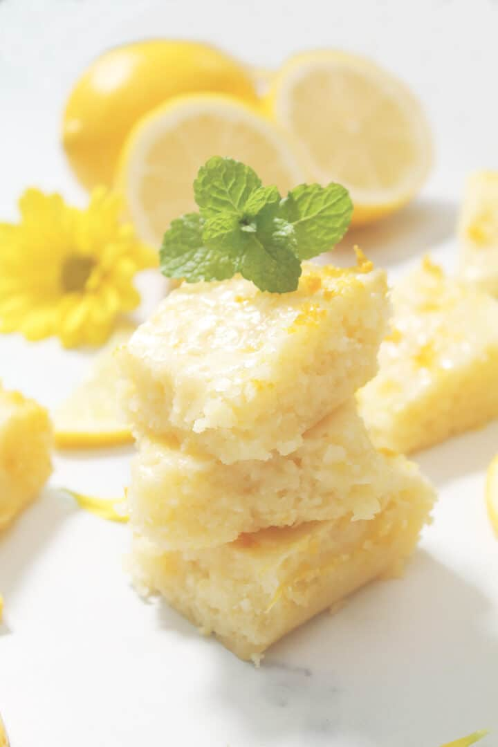 Stacked lemon brownies on white marble table with mint leaf on top.