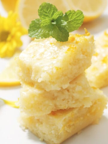 Stacked lemon blondies on white marble table with mint sprig and yellow daisy.