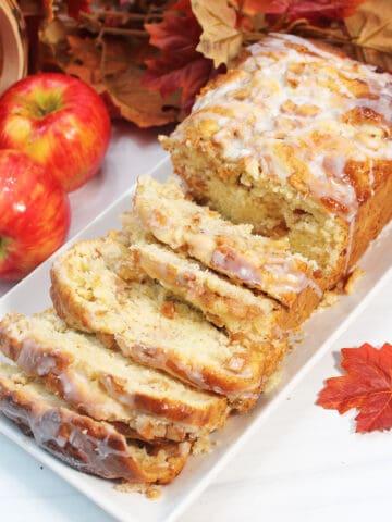 Sliced glazed apple cinnamon bread on white platter with apples.