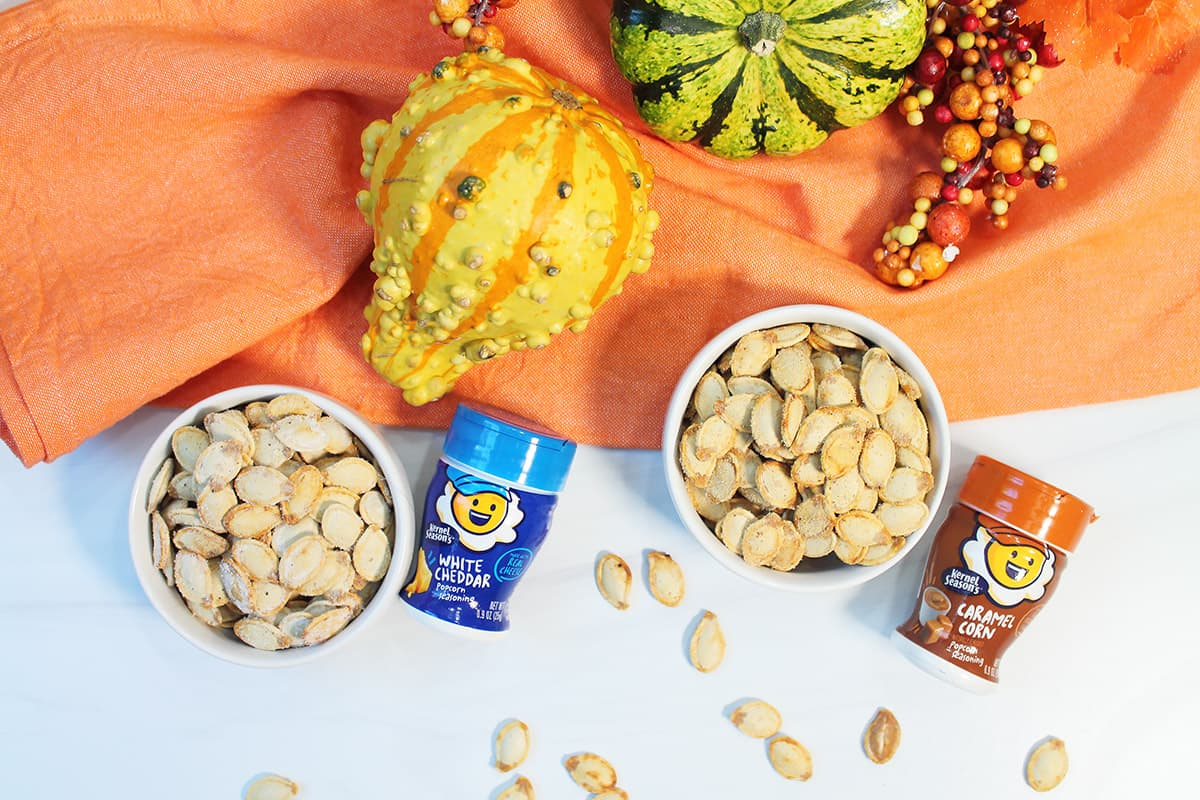 Two bowls of roasted pumpkin seeds with flavorings beside them.