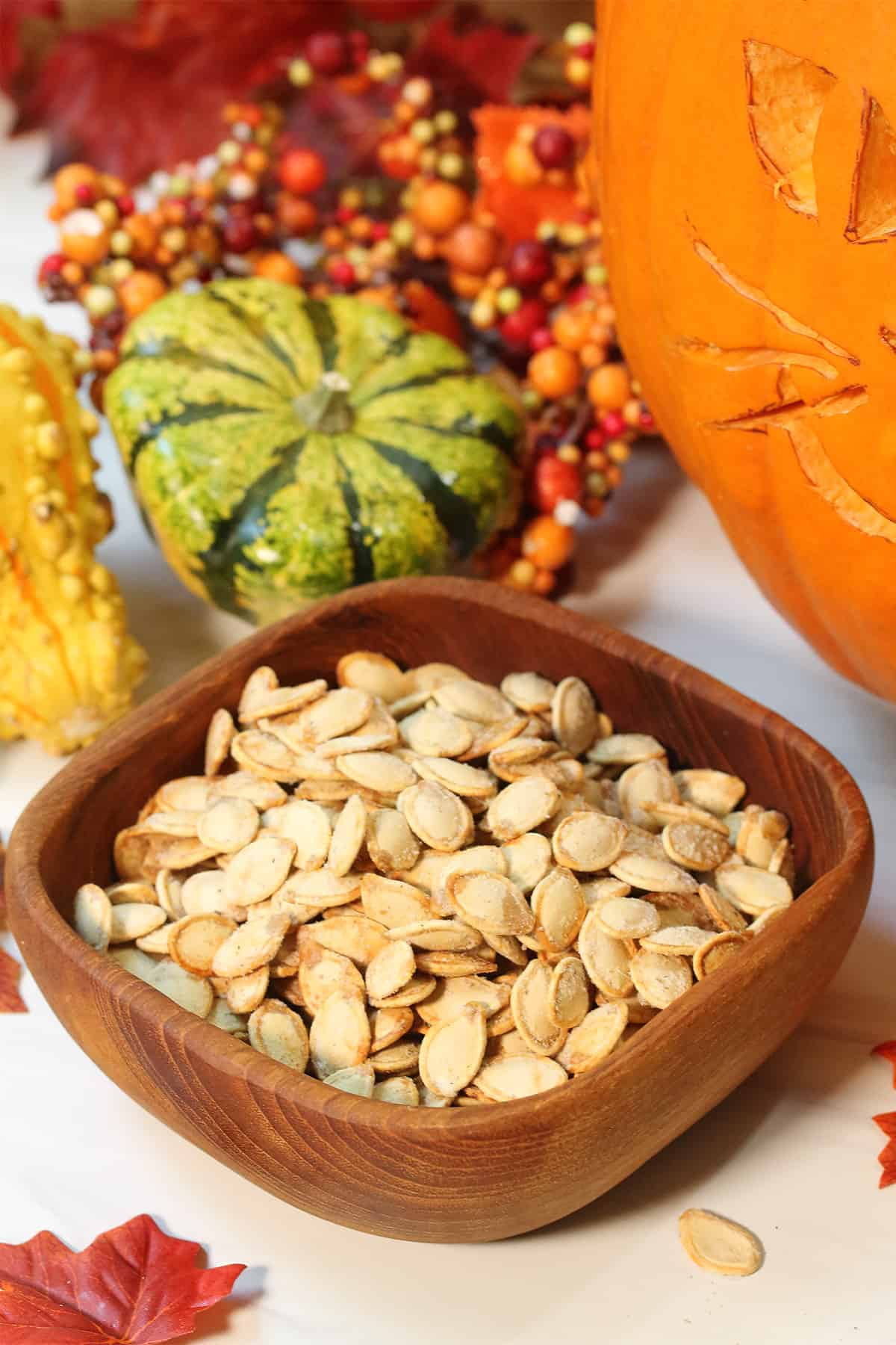 Air fried pumpkin seeds in wooden bowl with colorful gourds in back.