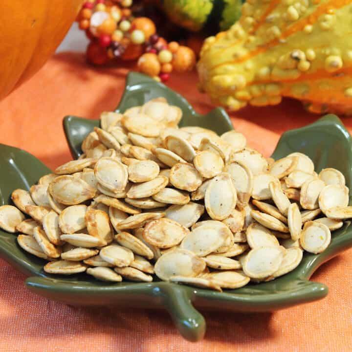 Closeup of pumpkin seeds in green leaf bowl on orange napkin.