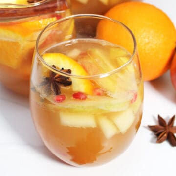 Closeup of glass of sangria with fruit and star anise in it.