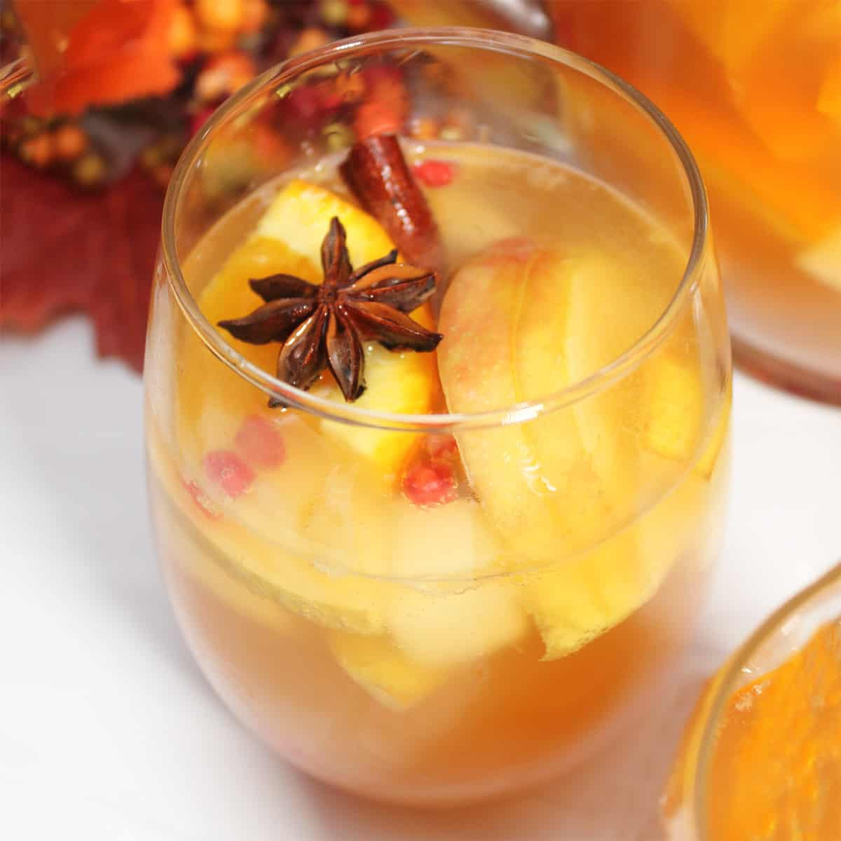 Closeup of glass filled with sangria with star anise and cinnamon stick garnish.