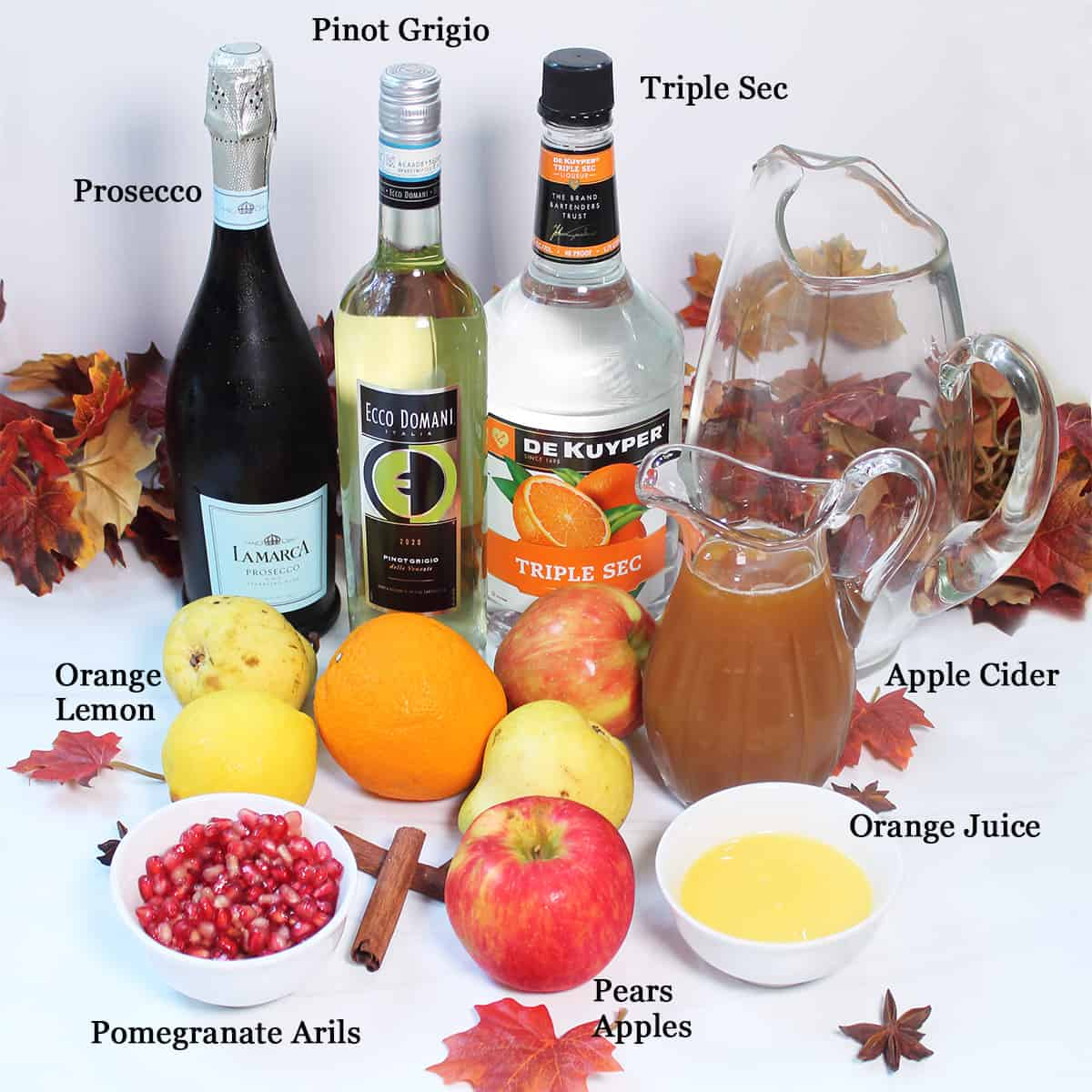Ingredients for apple cider sangria on white table.