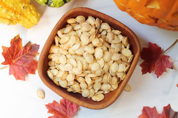 Overhead of pumpkin seeds in wooden bowl on white table with fall leaves.
