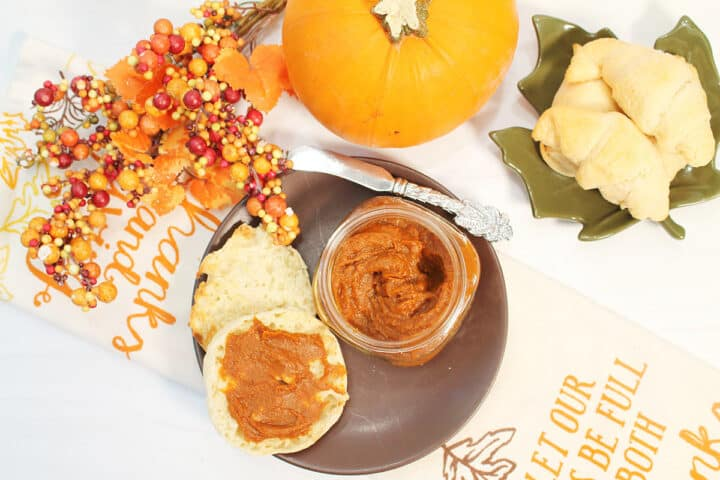 Overhead of pumpkin spread on muffin on brown plate with jar next to it.