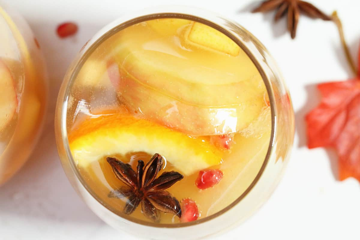 Overhead of glass of sangria on white table showing pieces of fruit and star anise.