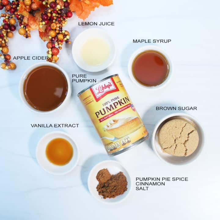 Overhead of ingredients for butter on white table.