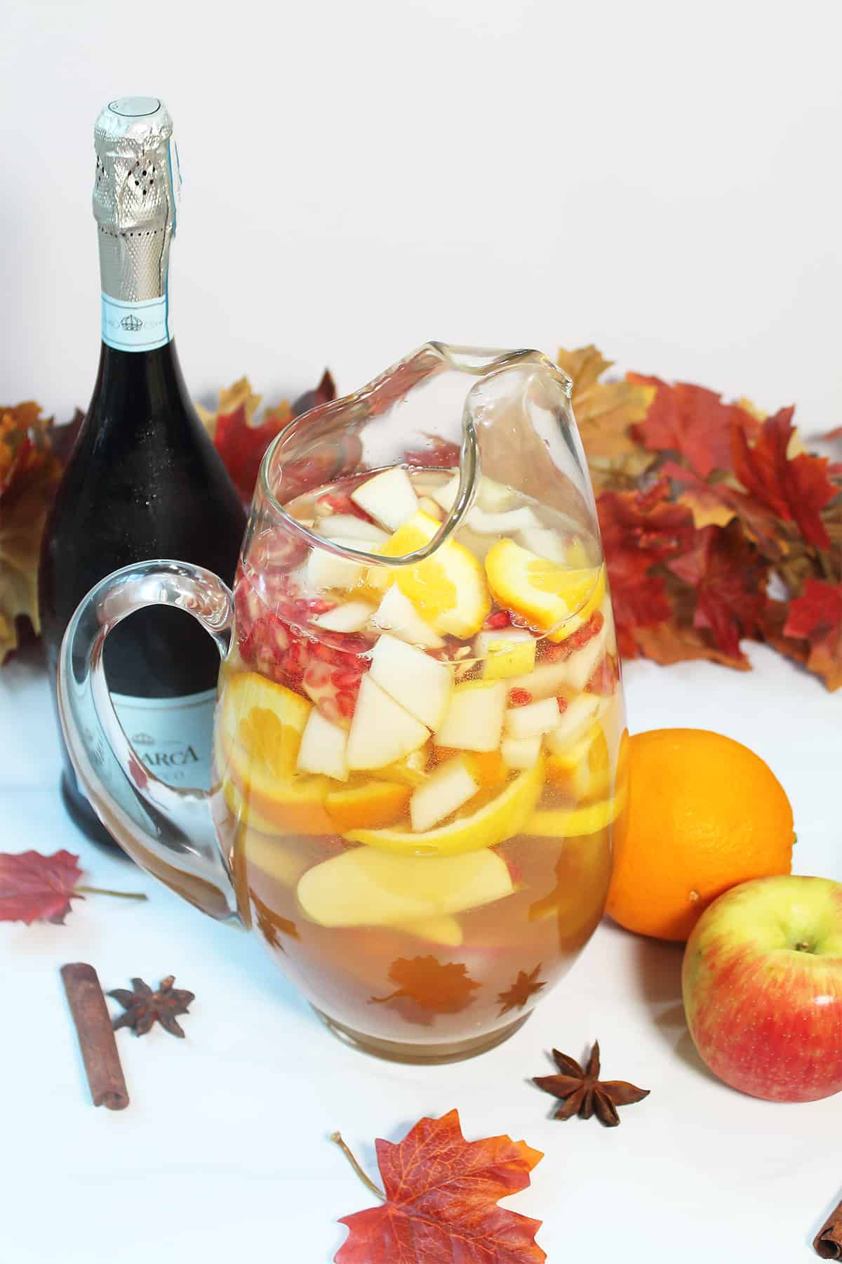 Fall sangria in pitcher with prosecco bottle and fall leaves.