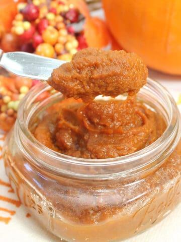 Scoop of pumpkin butter over jar with pumpkin in back.