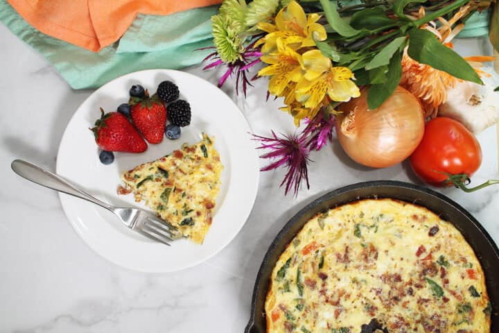 Overhead of serving on plate next to breakfast frittata in iron skillet. Vegetables and flowers around them.
